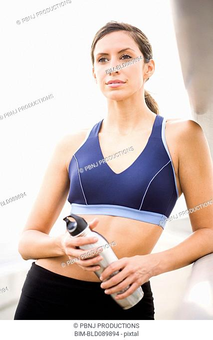 Hispanic woman in sportswear holding water bottle