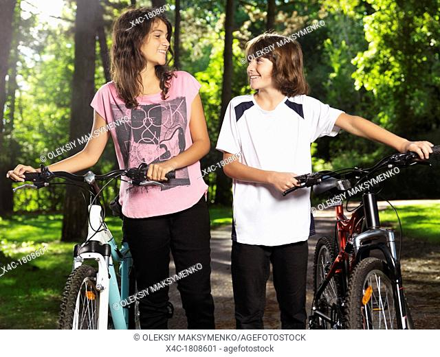 Two happy smiling children, brother and sister, 10 and 13, walking with bicycles in a park