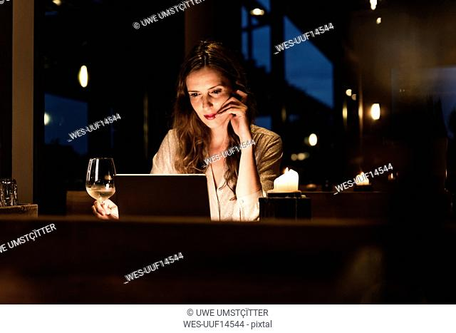 Woman having glass of white wine looking at laptop