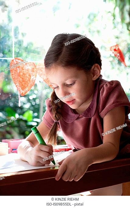 Girl sitting at window table drawing with crayon