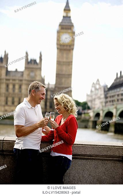 A middle-aged couple in front of the Houses of Parliament, drinking champagne