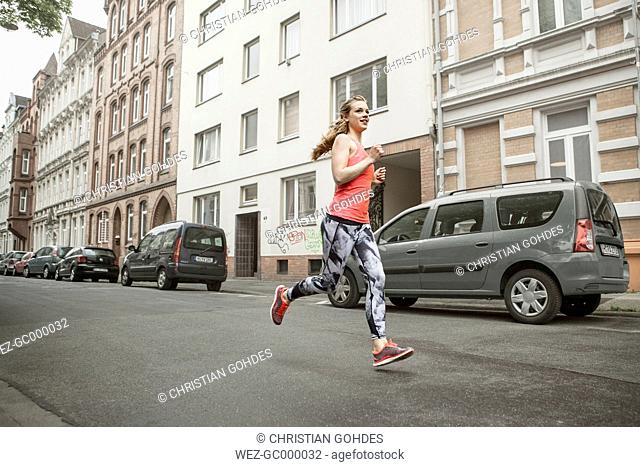 Germany, Lower Saxony, Hanover, young female jogger running on a street