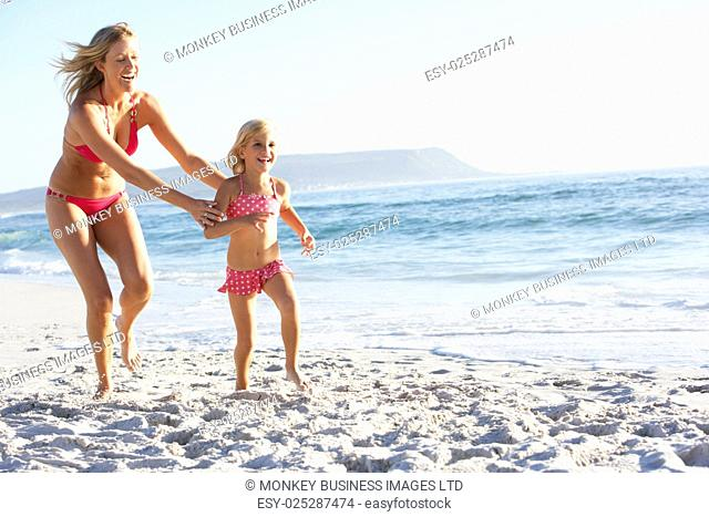 Mother And Daughter Running Along Beach Together Wearing Swimming Costume