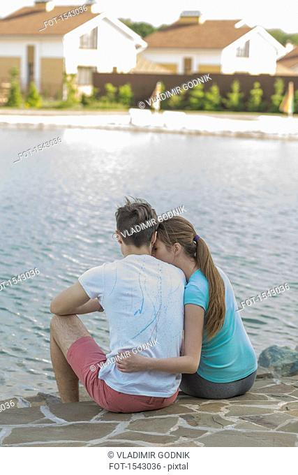 Rear view of couple sitting at lakeshore in town