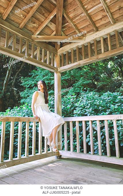 Young Japanese woman on wooden deck in a city park