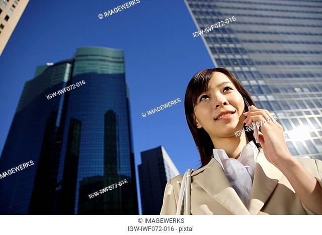 Japan, Honshu, Tokyo, Businesswoman using mobile phone, low angle view