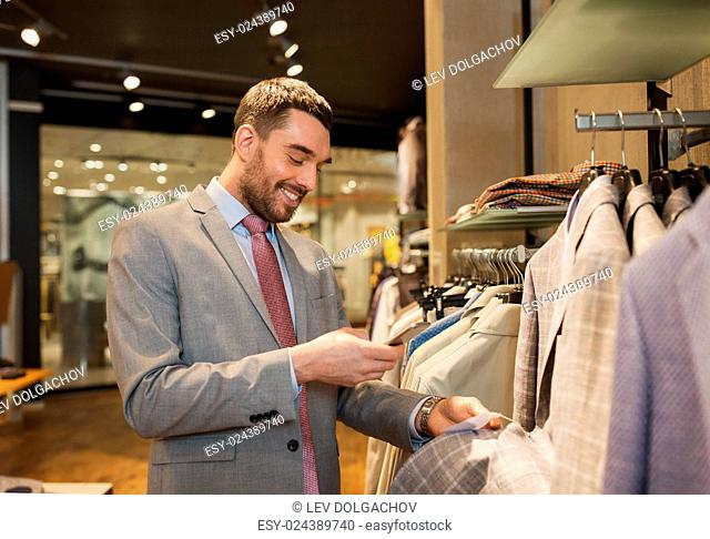 sale, shopping, fashion, technology and people concept - happy man or businessman in suit with smartphone choosing clothes at clothing store