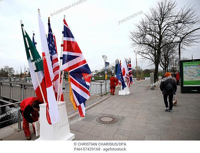 Helpers stick flags into a pedestal next to a bridge of the river Trave in Luebeck, Germany, 14 April 2015. The meeting of the G7 foreign ministers will take...