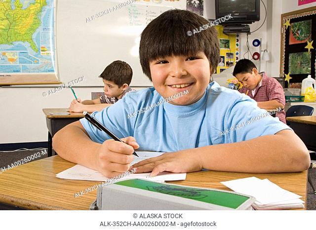 Alaskan native boy in classroom at desk inside Alaska