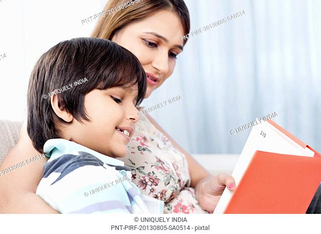 Boy reading a book with his mother