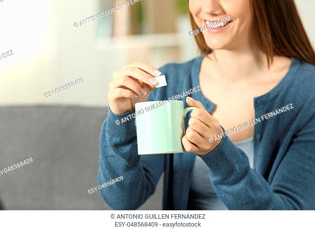 Close up of a smiley woman throwing sugar into coffee mug sitting on a couch in the living room at home