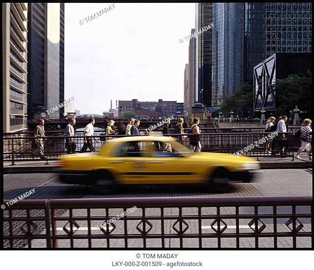 Commuters walk over city bridge with speeding cab in foreground