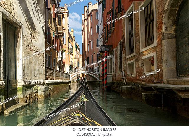 Close up of part gondola with canal bridge in distance, Venice, Veneto, Italy