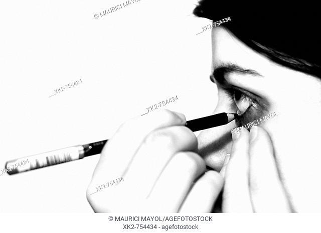 Chica maquillandose la raya del ojo