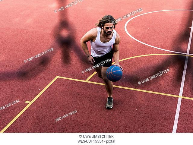Young man playing basketball on basketball ground