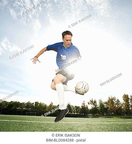 Caucasian soccer player kicking soccer ball