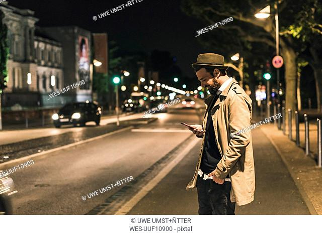 Stylish young man with cell phone on urban street at night