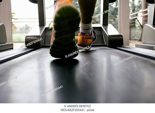Feet of man running on a treadmill