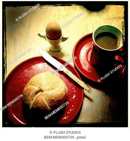 Egg, roll and coffee breakfast on table
