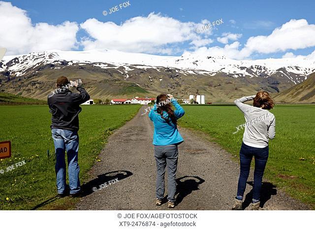tourists take photos at the thorvaldseyri family farm beneath eyjafjallajokull iceland