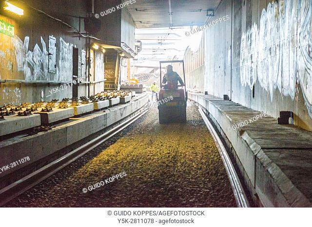 Rotterdam, Netherlands. Small shovel working inside a train tunnel on the foundations of a new to build railroadtrack