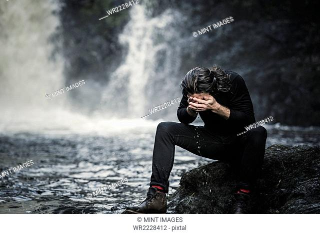 A man sitting washing his face in a mountain stream by a waterfall