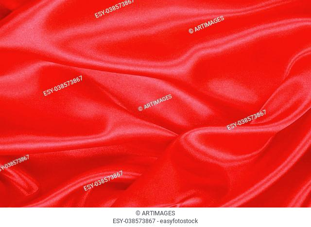 Red Silk cloth of abstract background or wavy folds or satiny silk texture satin velvet material or elegant wallpaper design curve