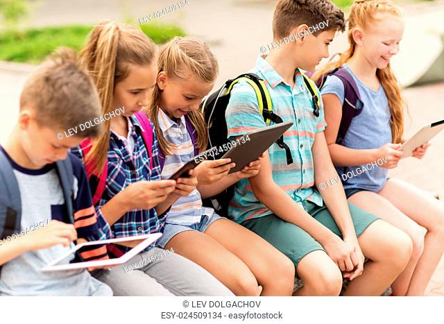 primary education, friendship, childhood, technology and people concept - group of happy elementary school students with backpacks sitting on bench and talking...