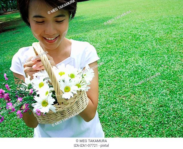 Portrait of a young woman holding a basket of flowers and smiling
