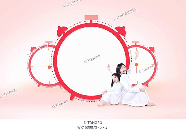 a mother and a daughter next to an alarm clock with a copy space