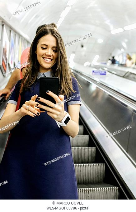 UK, London, portrait of smiling businesswoman standing on escalator looking at cell phone