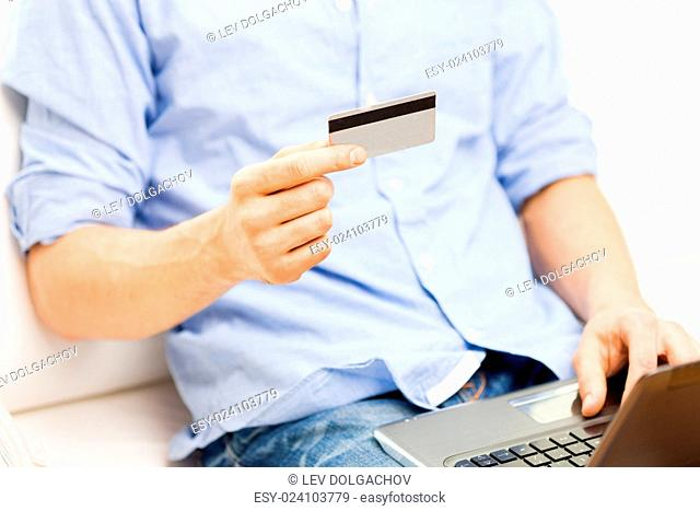 technology, people and online shopping concept - close up of man with laptop computer and credit card at home