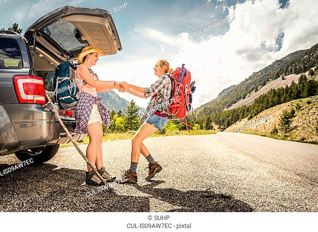 Teenage girl hiker pulling friend from car boot, Red Lodge, Montana, USA