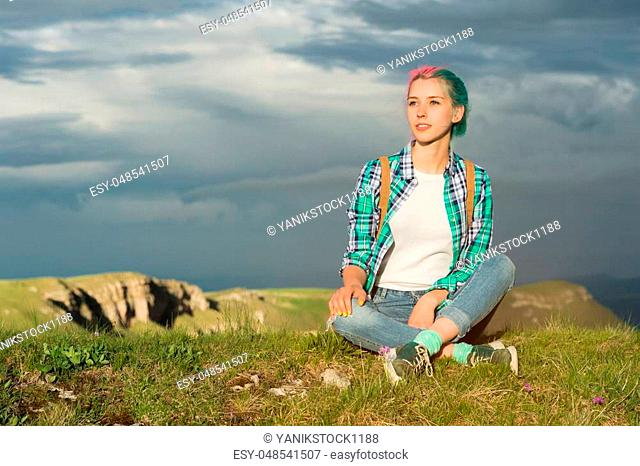 Portrait of young smiling woman traveler with multi-colored hair. Sitting high in the mountains in the evening with a decline in the background of a plateau