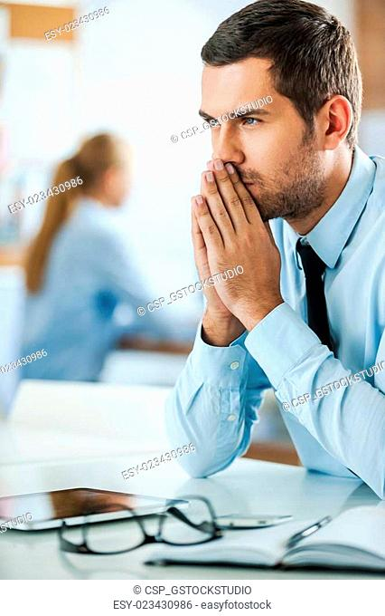 Thinking about solution. Serious young businessman in formalwear keeping hands clasped while sitting at his working place