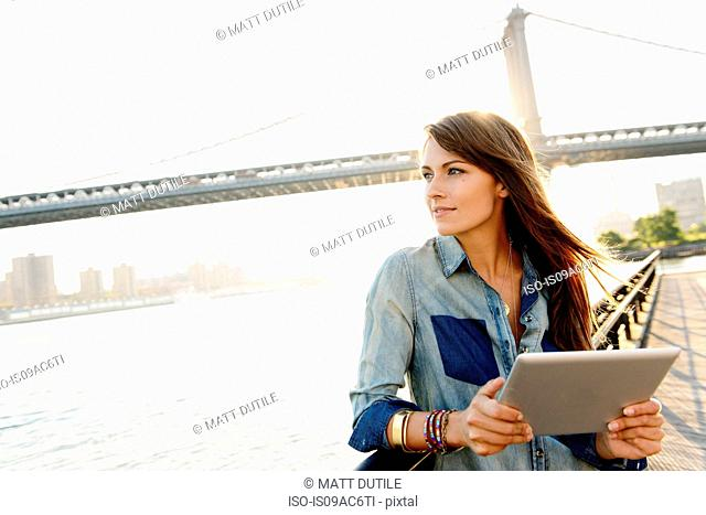 Young woman with digital tablet, Manhattan Bridge, Brooklyn, USA