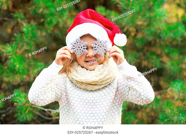 Christmas and people concept - little girl child in santa red hat with snowflakes on the eyes