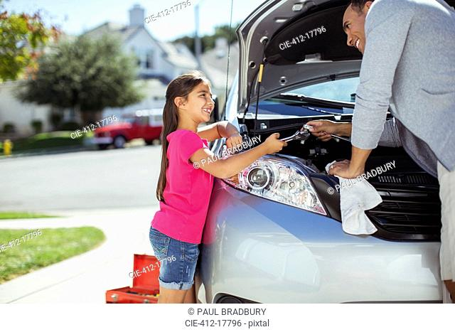 Father and daughter fixing car engine