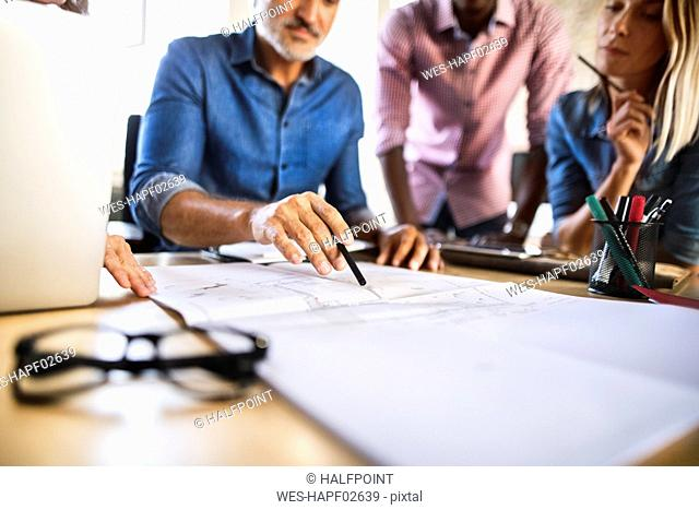 Colleagues discussing blueprint at desk in office