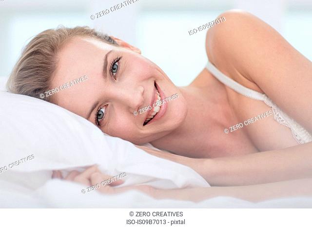 Portrait of young woman lying in bed, smiling