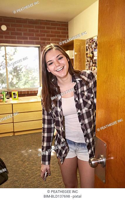 Caucasian student smiling in dorm room