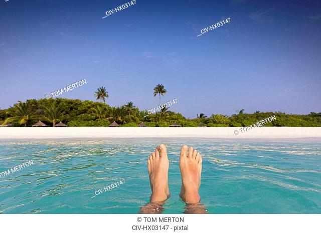 Personal perspective barefoot man floating in tropical ocean with beach view