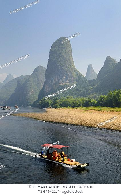 Tour boat raft traveling down the Li river with tall karst mountain cones in background. Guangxi, China