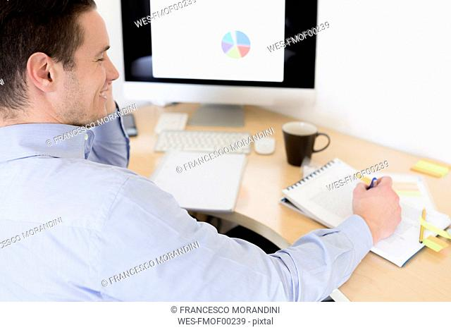 Smiling businessman on the phone at desk