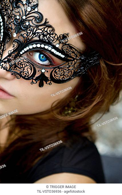 Close up of young woman wearing a mask looking at the viewer