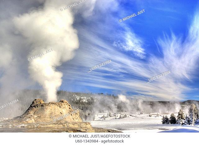 Castle Geyser erupts under a bright sky at Yellowstone National Park