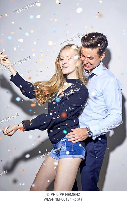 Young couple dancing under shower of confetti