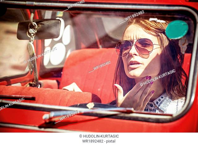 Portrait of young woman with sunglasses in red car
