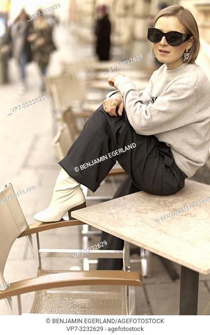 fashionable blogger woman sitting on table of street café outdoors, streetstyle, in Munich, Bavaria, Germany