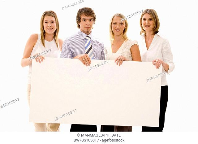 Four business people holding a large blank sign